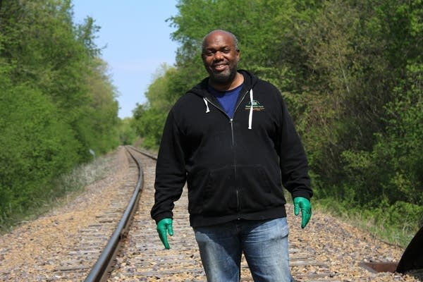 A man stands along train tracks