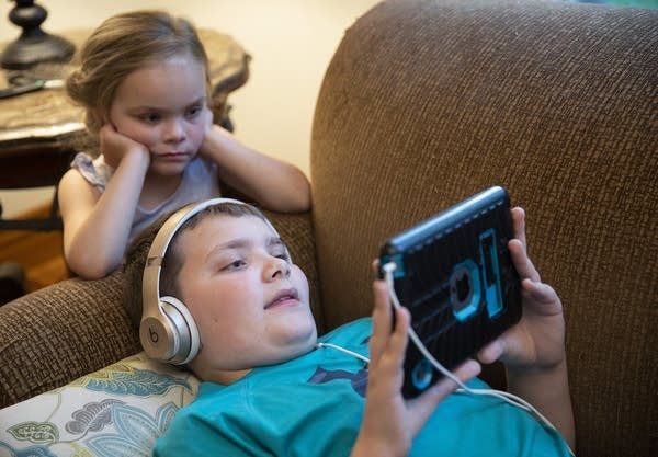 Parker Barnes, 12, watches videos with his 4-year-old sister, Greta.