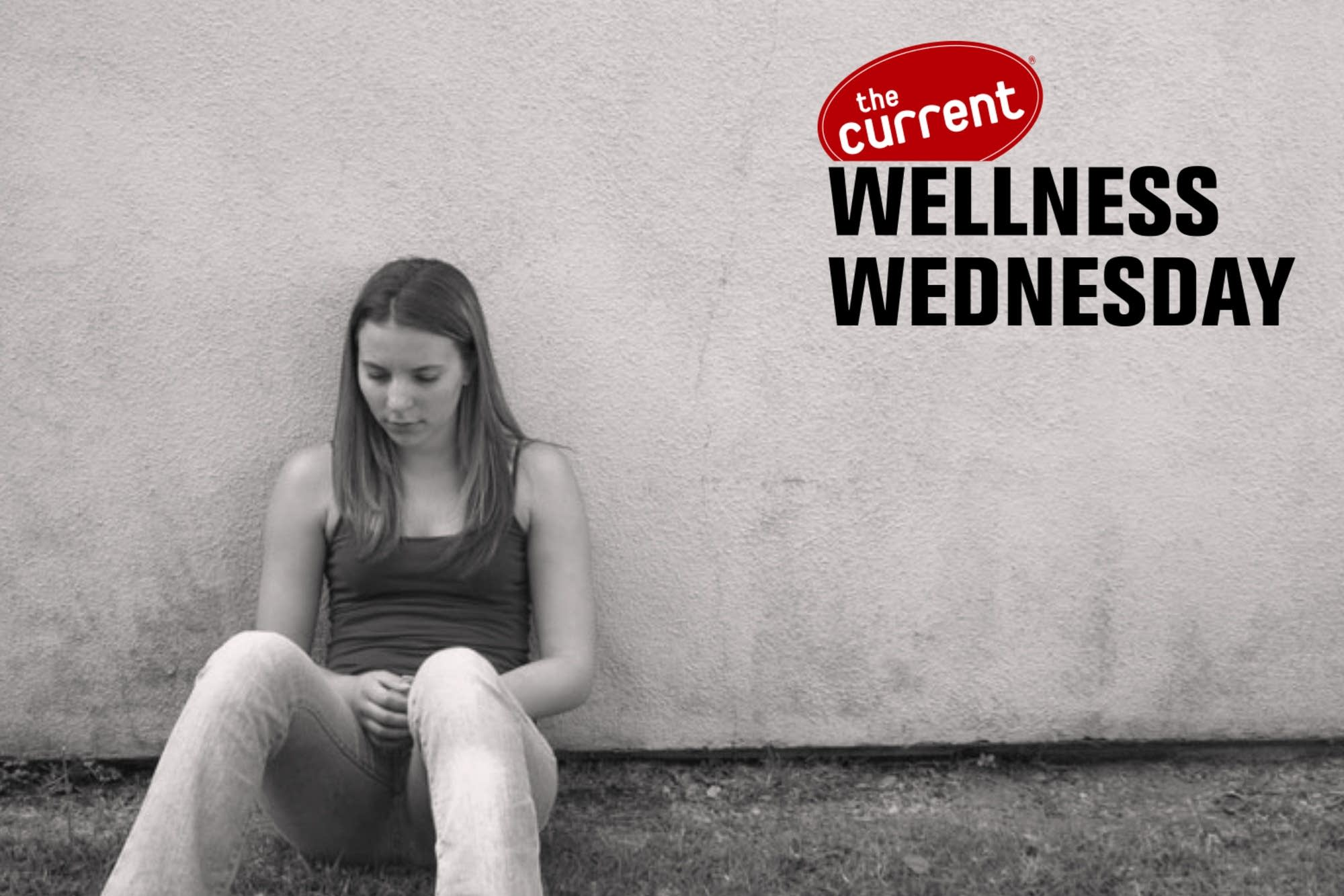 Young woman sitting against blank wall looking reflective.