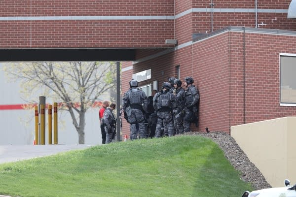 Police in tactical gear stand outside of a bank.