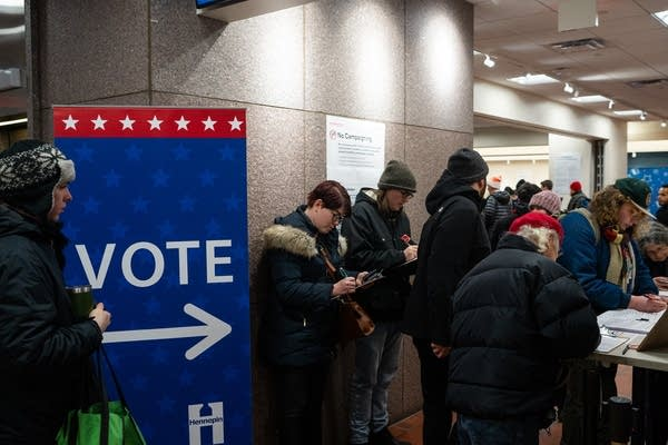 People line up in front of a voting sign.