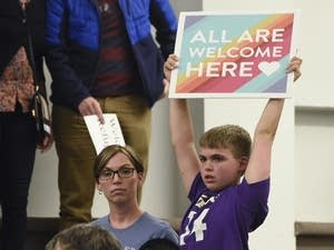 A child holds a sign during a city council meeting on refugees.