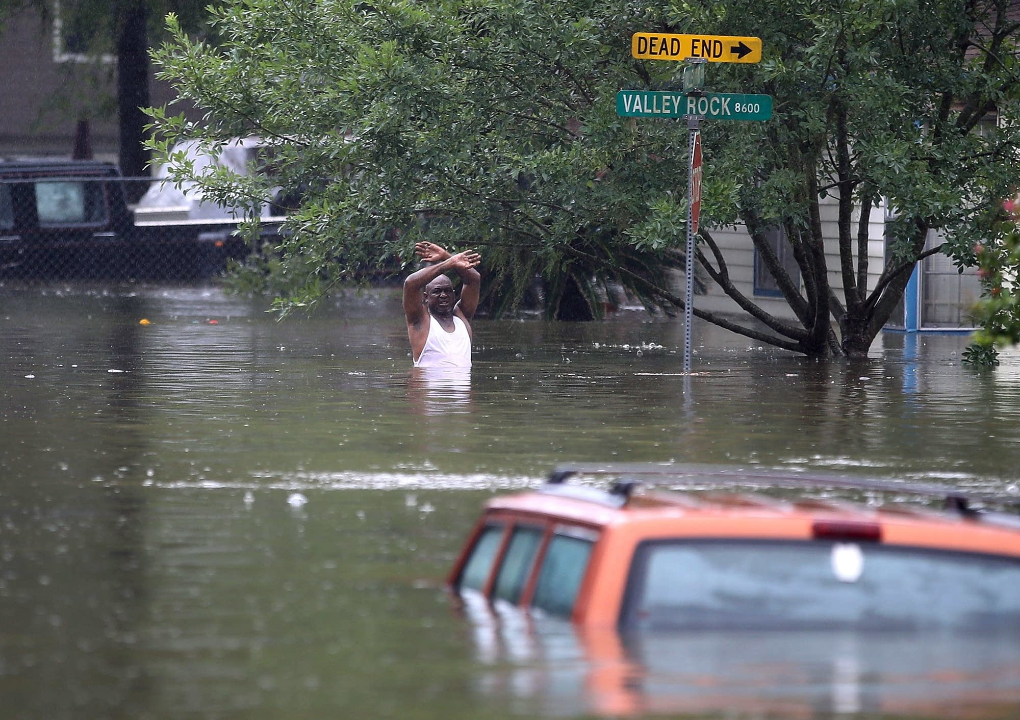 A man waves down a rescue crew as he tries to leave the area.