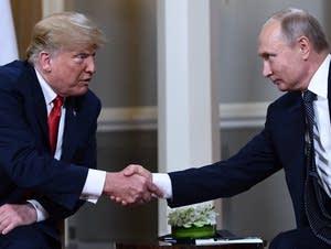 Russian President Vladimir Putin, right, and President Trump shake hands.