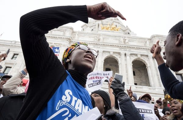 Organizer Fata Acquoi, right, sings with attendees at a rally.
