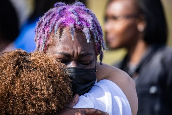 A woman with purple hair gives a hug.