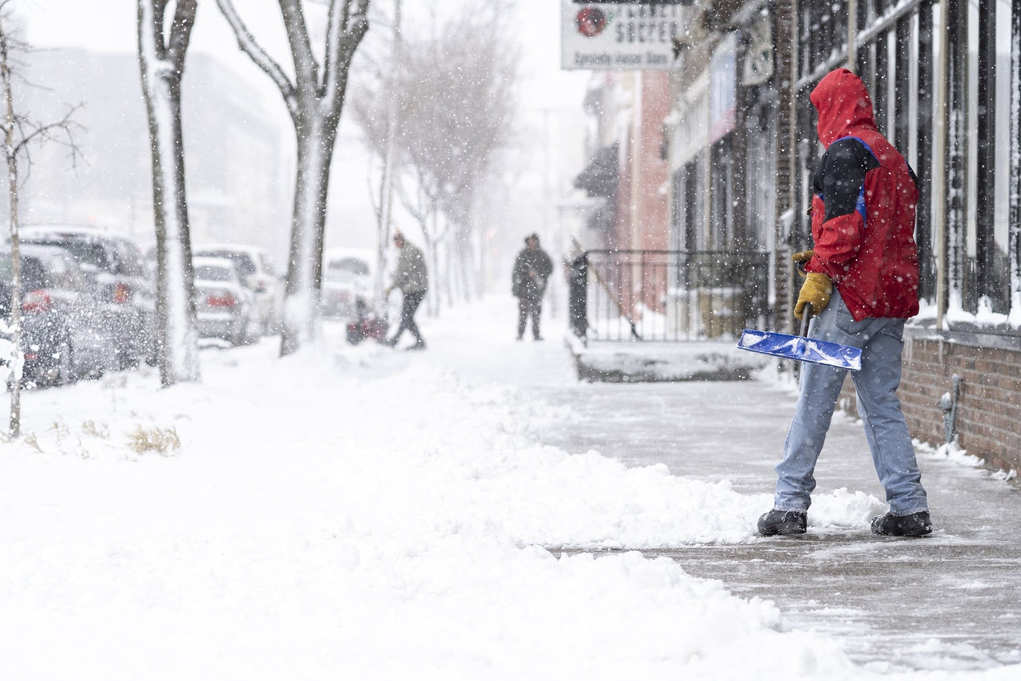 People clear snow from the sidewalk of Lyndale Avenue.