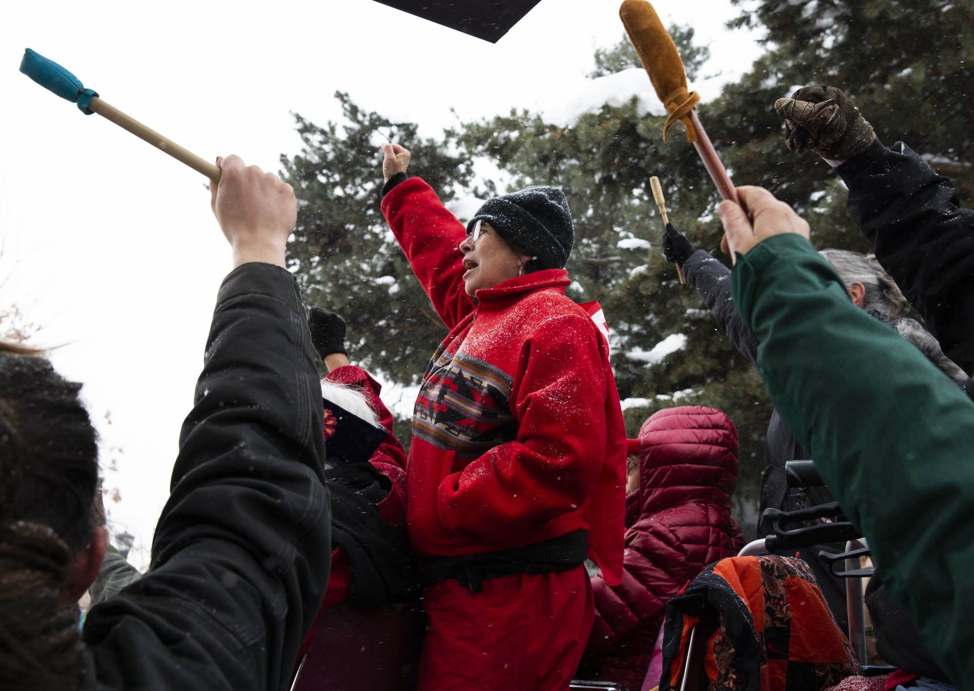 Pam Gokey raises her arms at the end of the march.