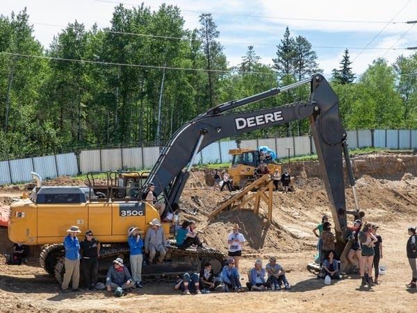 Activists gather around construction equipment.