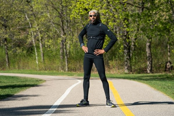 A man in running gear stands on a path.