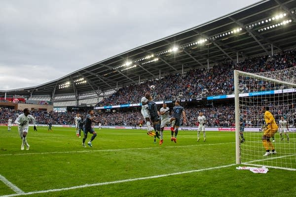Players from Minnesota United and New York City FC go up for the ball.