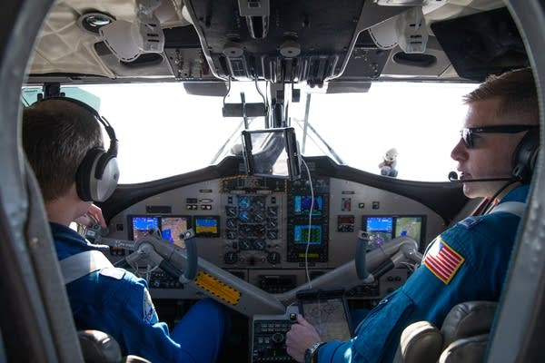Two pilots in blue jumpsuits sit in the cockpit of an airplane.