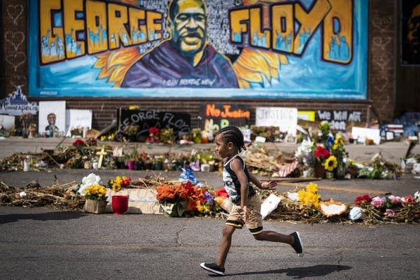 A 3-year-old runs past a mural at the George Floyd memorial