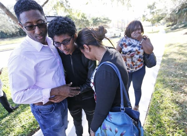 Family members embrace after a student walked out from the school.