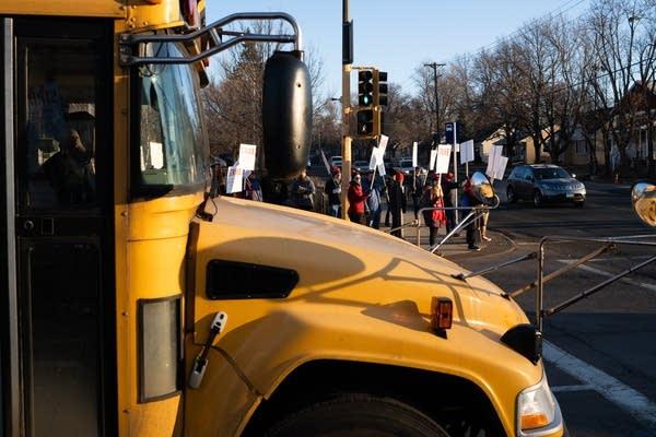 A school bus waits as teachers strike on the corner.