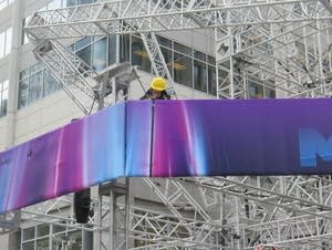 A worker begins removing a banner from scaffolding