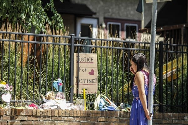 A neighborhood resident stops by the memorial for Justine Ruszczyk.