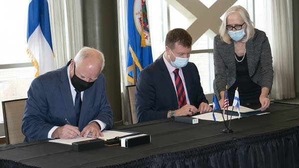 Two people sign documents at a desk.