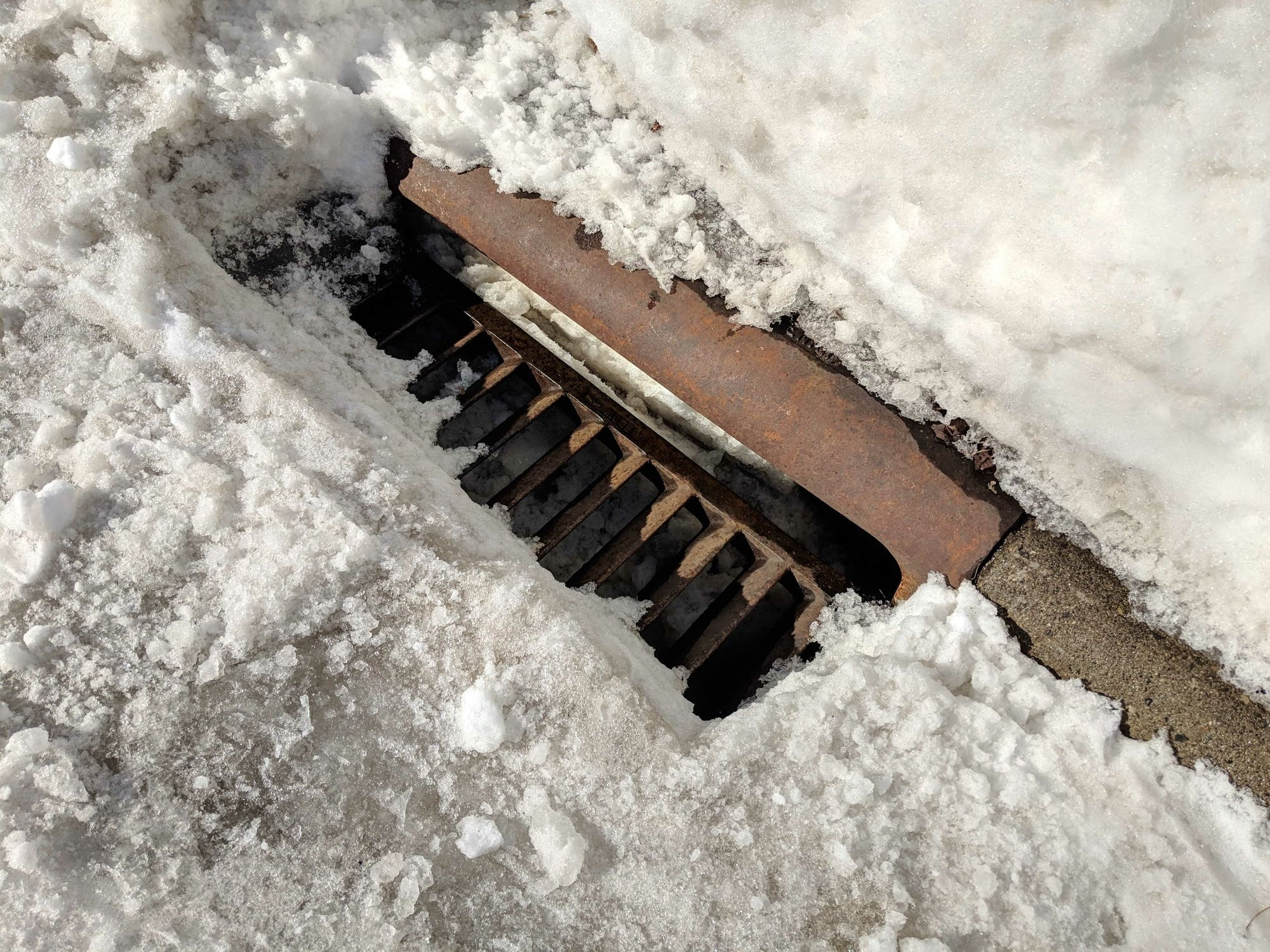 A storm drain catch basin on Fairmount Avenue in St. Paul is full of snow.