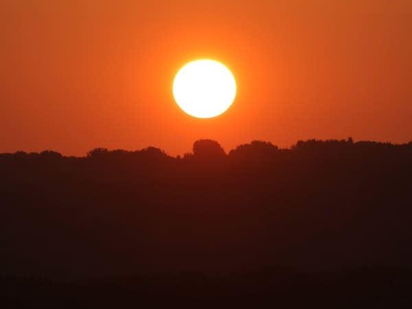The sun rises above the horizon