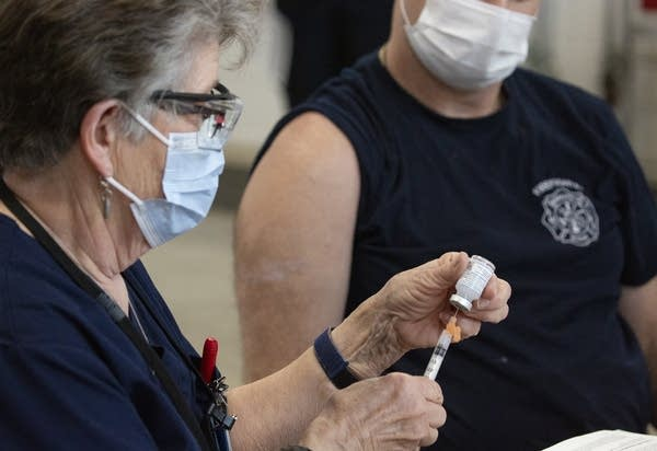 A nurse pulls a needle from a vaccine vial.