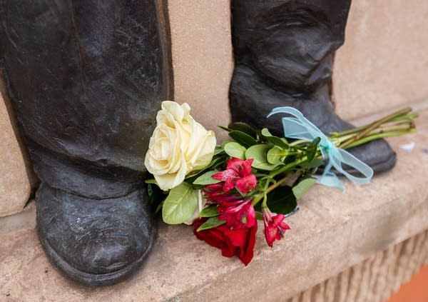 Flowers placed at the fee of a bronze statue.