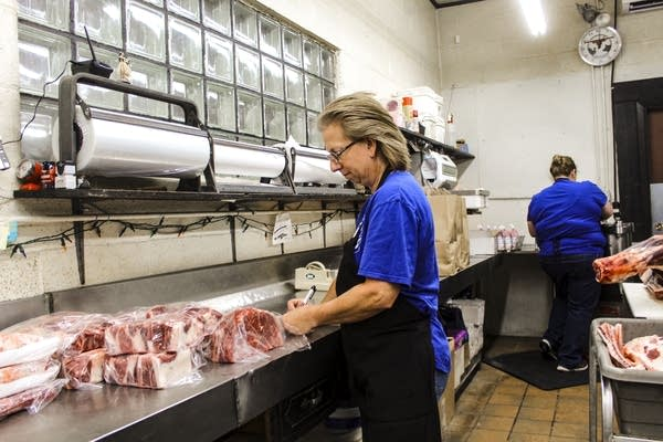 A woman wraps meat in plastic wrap at a counter.