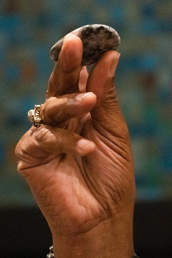 A smooth stone is held up in a hand.