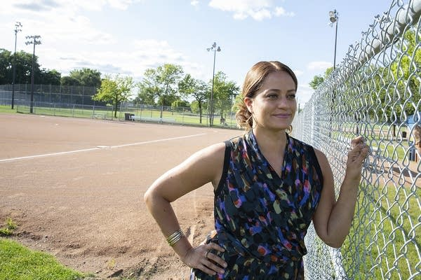 A woman stands near a metal fence at a softball field.