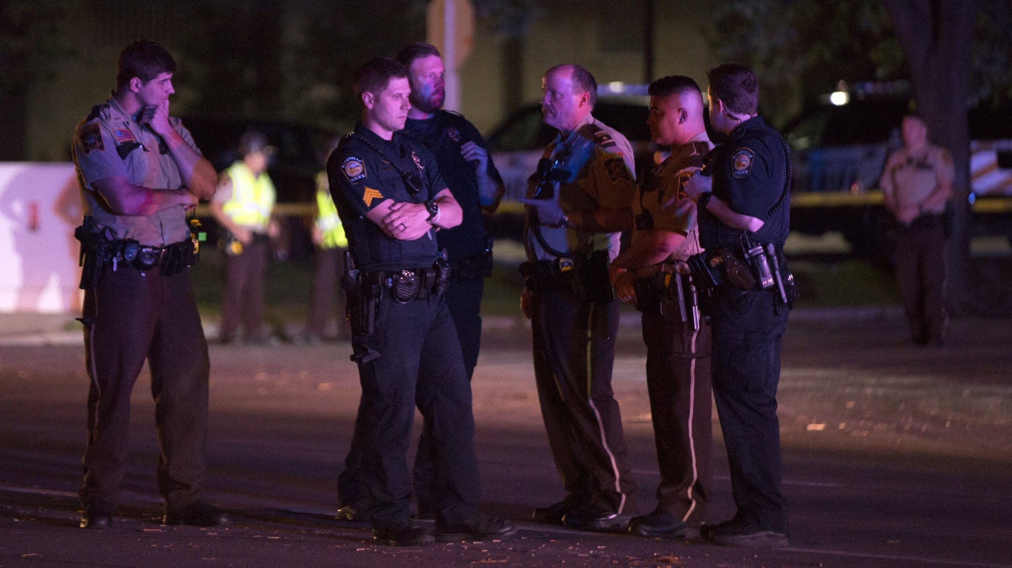 Officers gather at the scene of the shooting.