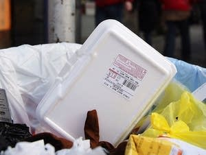 A styrofoam takeout container in the trash.