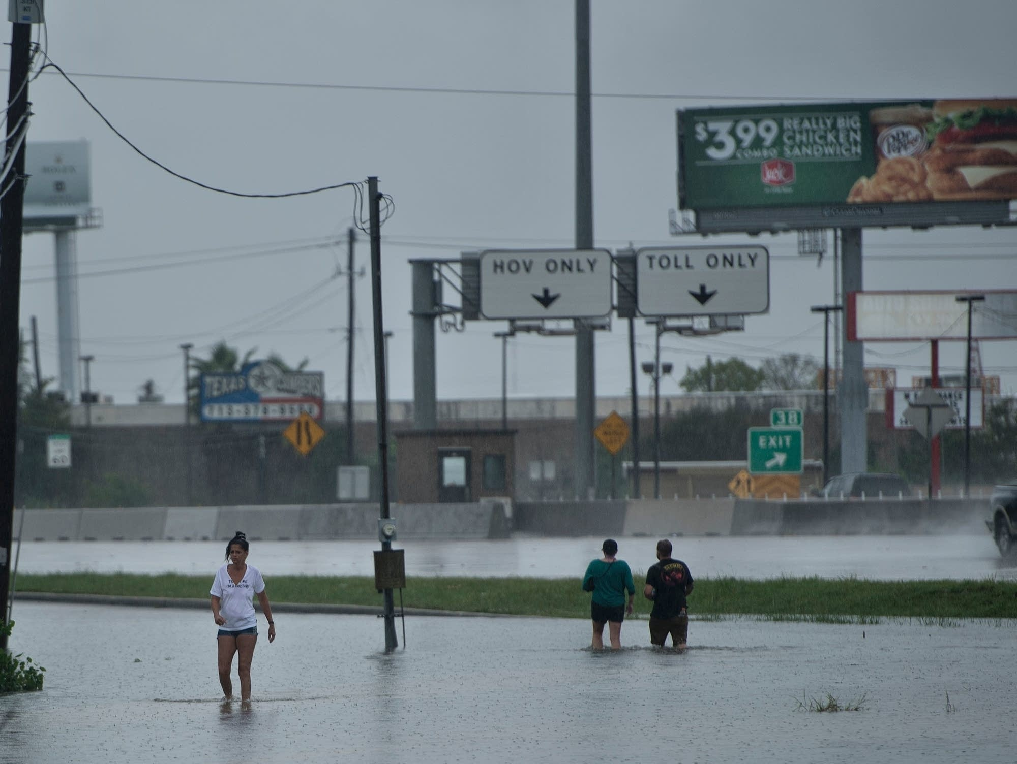 People walk through flooded streets
