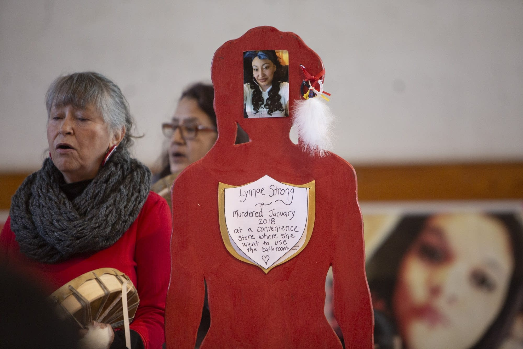 A photograph of Lynnae Strong is displayed at a rally.