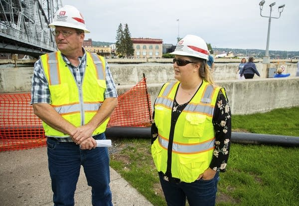 Two people wearing hard hats and safety vests stand in front of barriers
