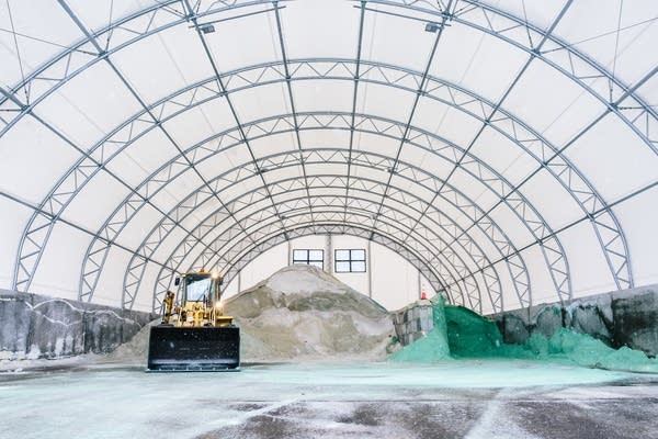 A front-end loader sits in front of piles of road salt.