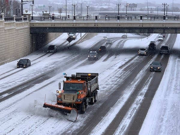 A Minnesota Department of Transportation plow clears snow