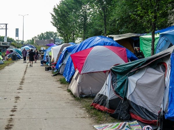 Dozens of tents are crammed into a patch of grass
