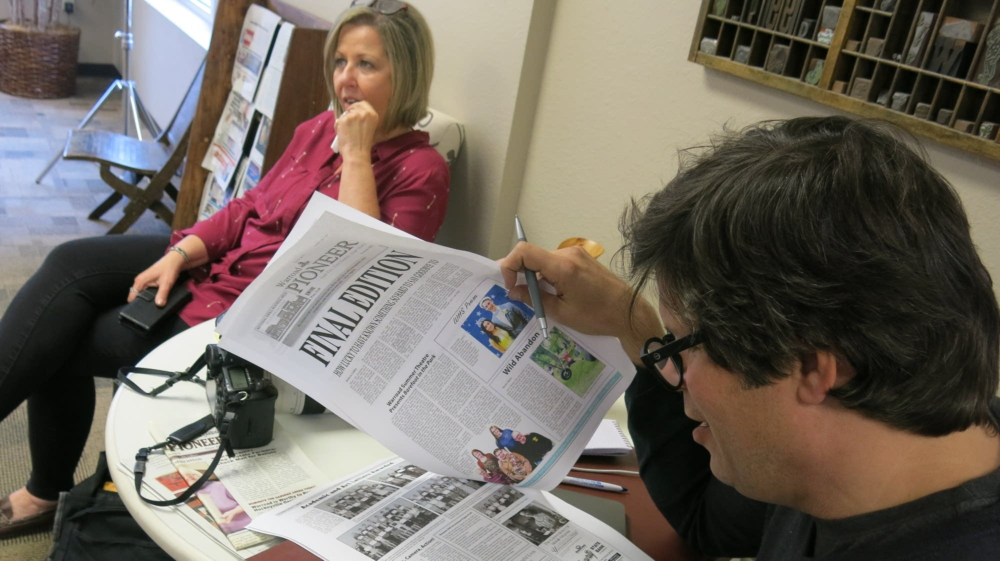 NYT writer Fausset reads a copy of the Warroad Pioneer's final edition.