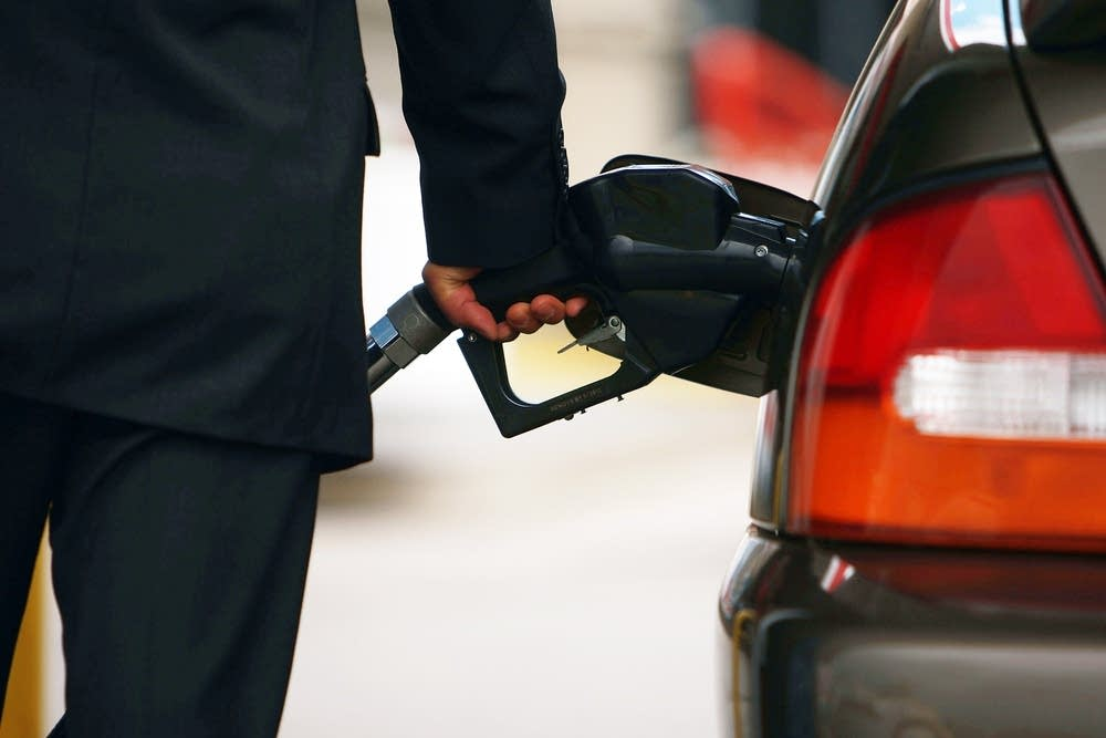 A driver puts fuel in his car.