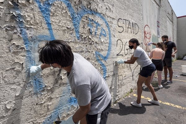 People clean graffiti from a wall