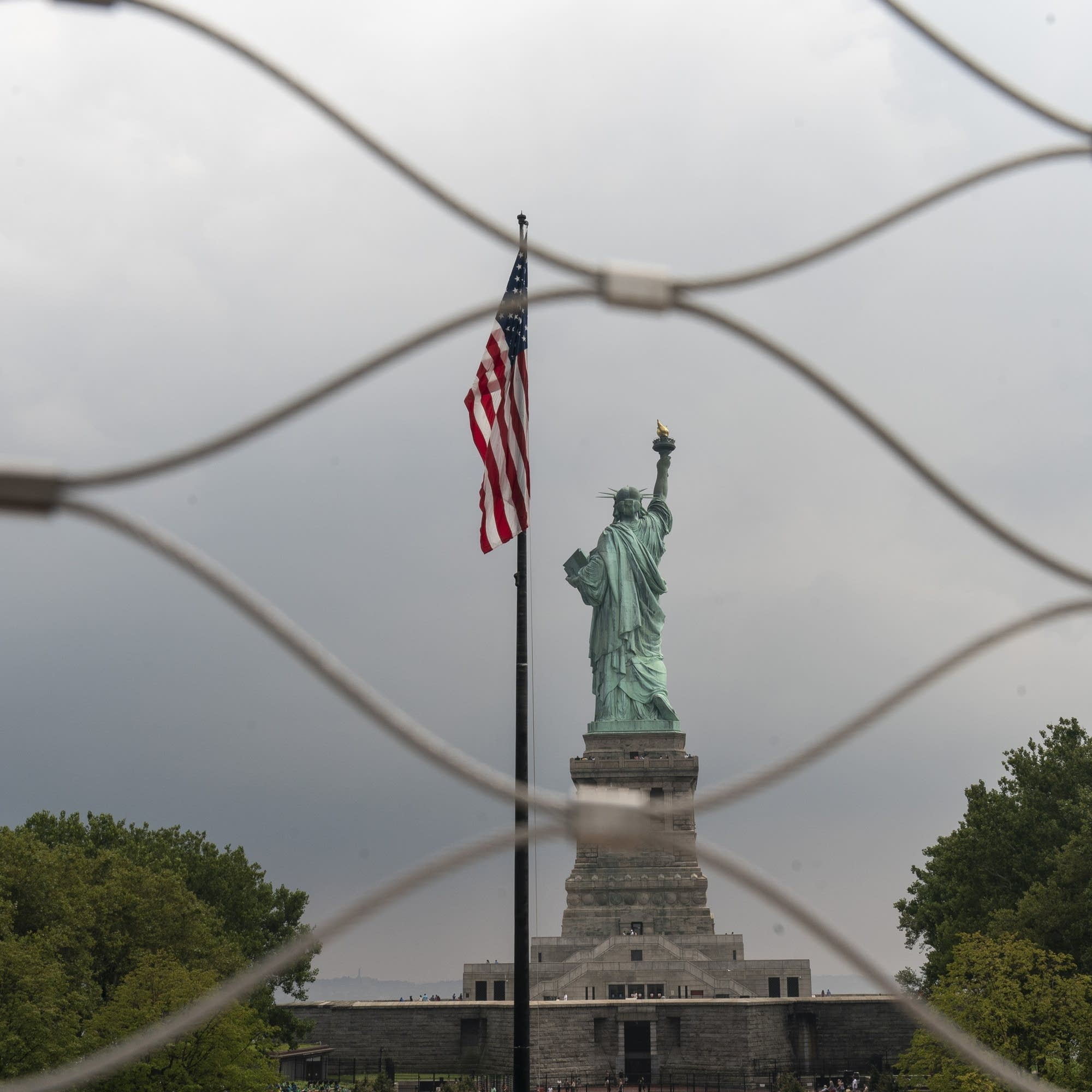 Statue of Liberty seen through a fence