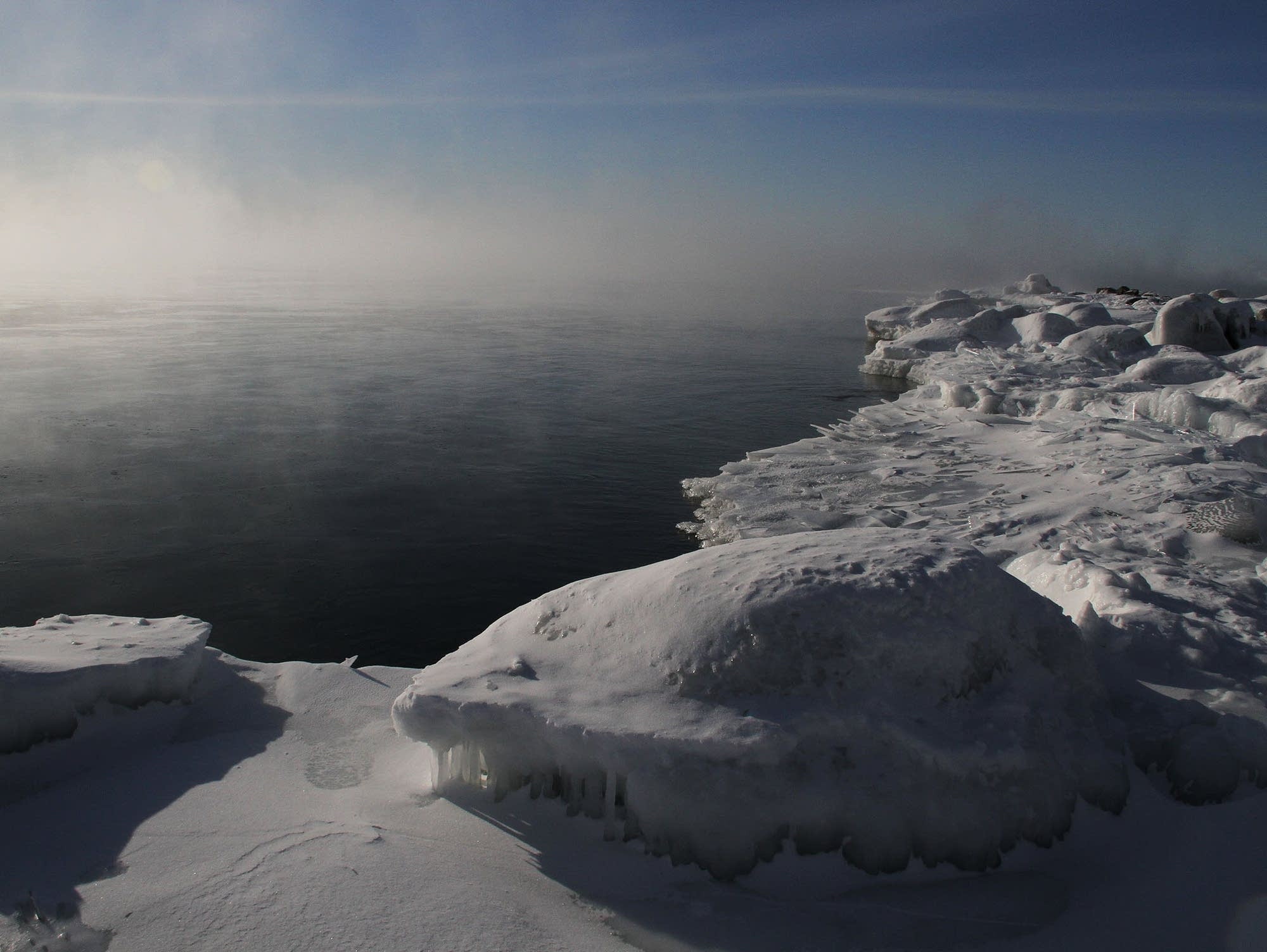 Sea smoke rises from a patch of open water on Lake Superior