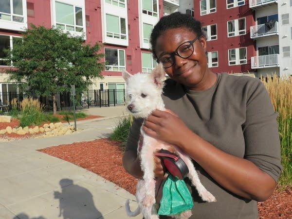 A woman stands in front of an apartment building while holding her dog.