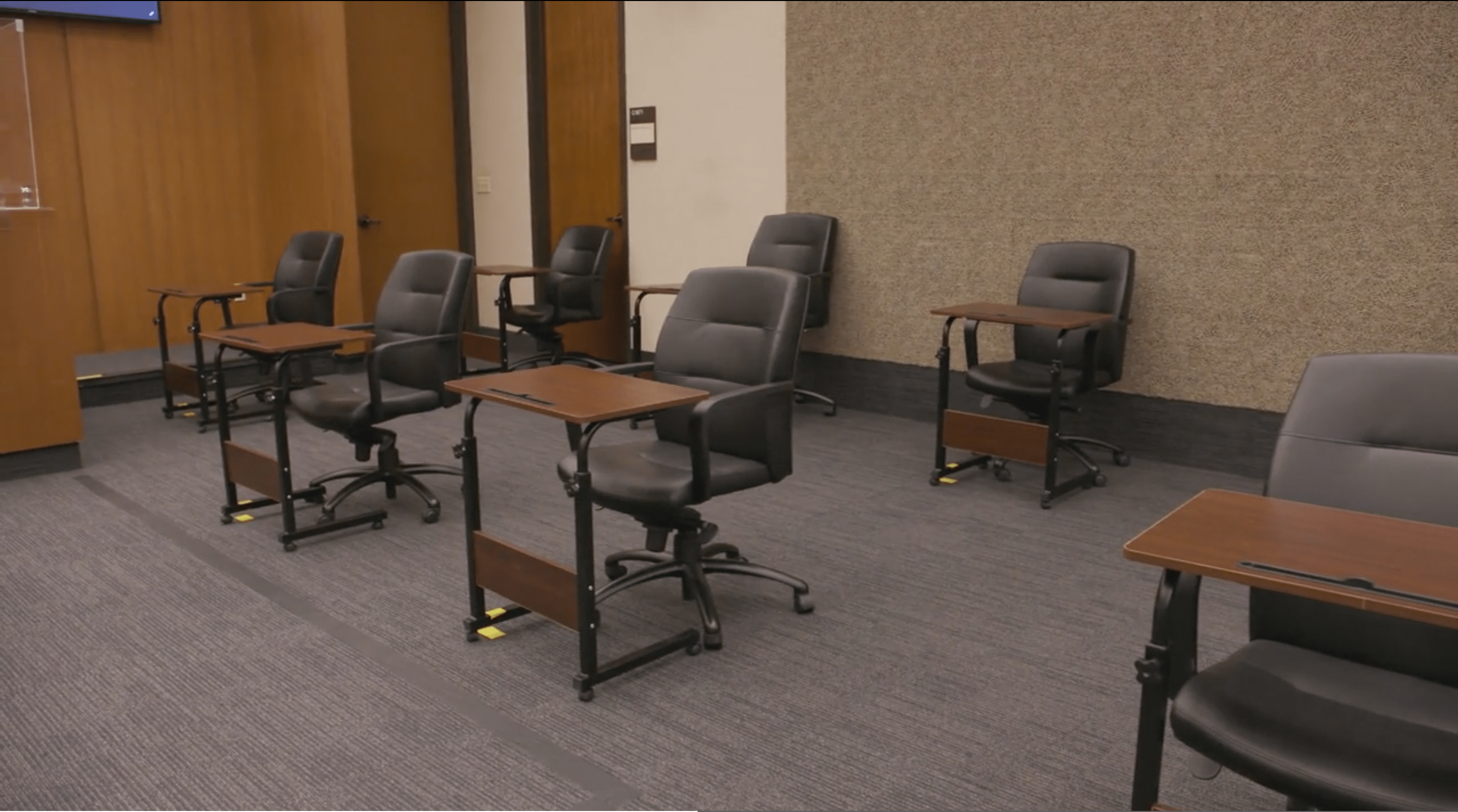 Jury chairs sit socially distanced in a court room.
