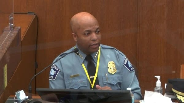A man in a police uniform speaks during testimony.
