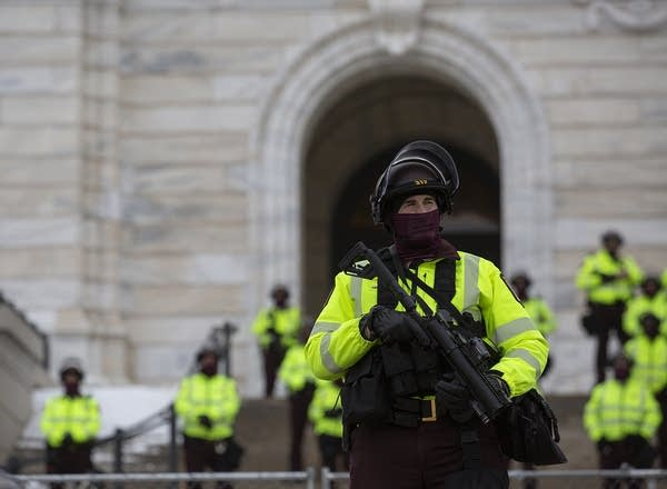 An armed law enforcement officer dressed in riot gear.