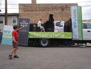 A boy cheers on Pop Up Classical's Concert Truck