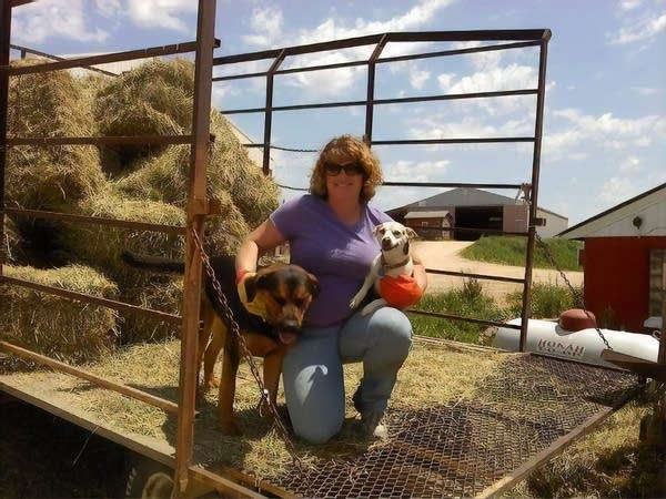 A woman poses with a dog on a trailer with hay.
