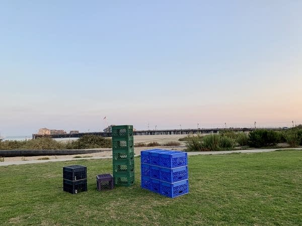 Milk crates (Black, Green & Blue) stacked in 3 formations in open grass