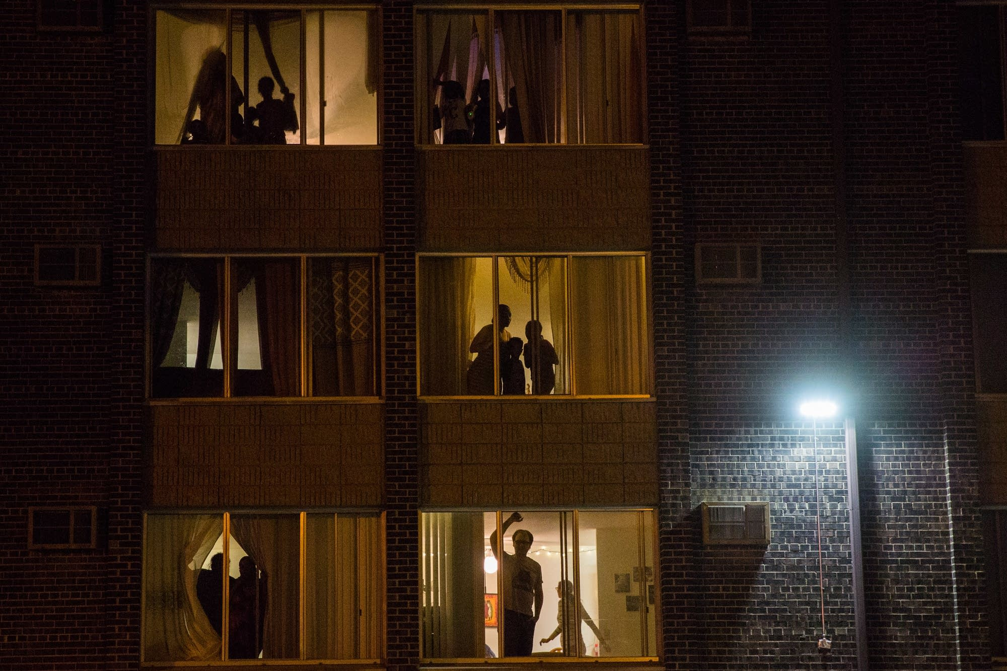 Residents watch from their apartments.